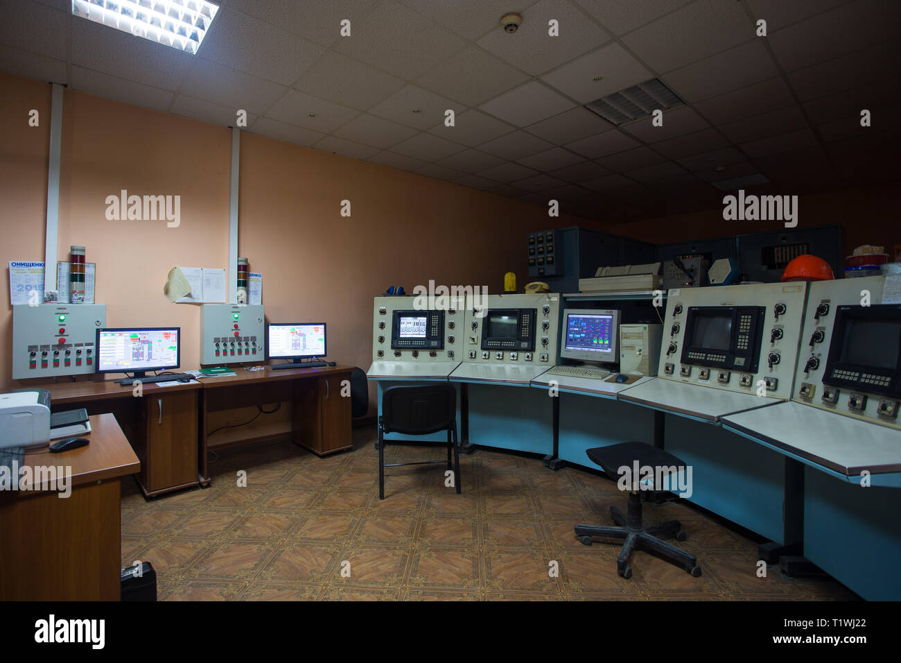 The theme of enterprise and plant automation. Inside the factory control center, monitors with information on the operation of the systems, workplace - Stock Image