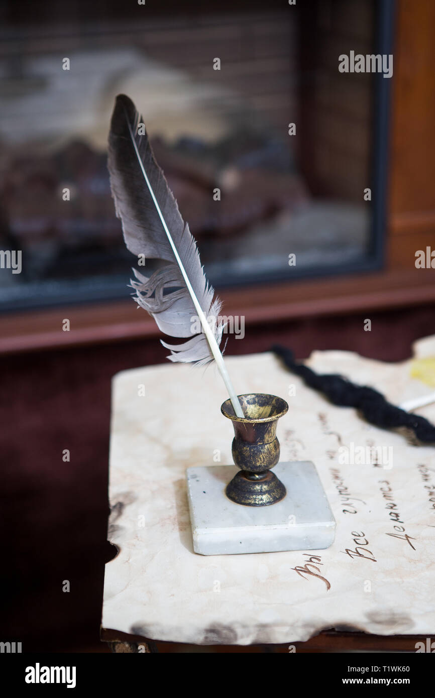 Old quill pen, books and vintage inkwell on wooden desk in the old office against the background of the bookcase and the rays of light. Conceptual Stock Photo