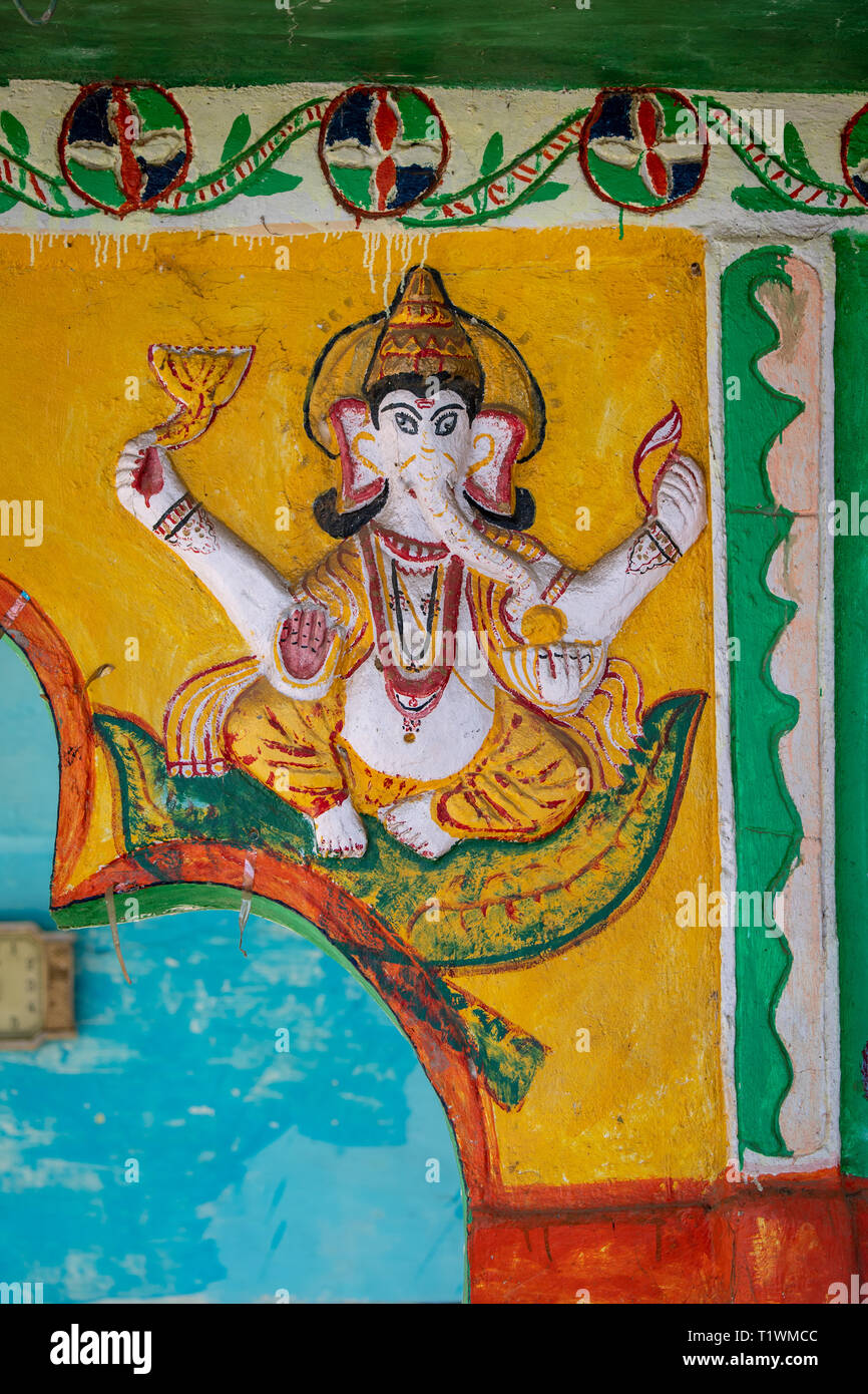 A variety of Hindu deities are carved and colorfully painted on the outside of a Hindu temple of worship in rural India - Stock Image