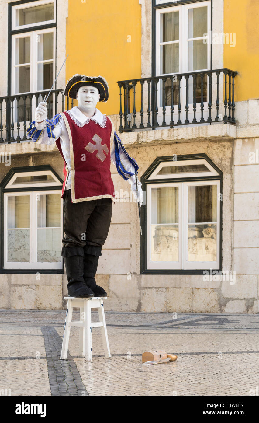 A street performer entertainer mime in traditional costume performing in central Lisbon, Portugal. Local travel sights and entertainment. - Stock Image
