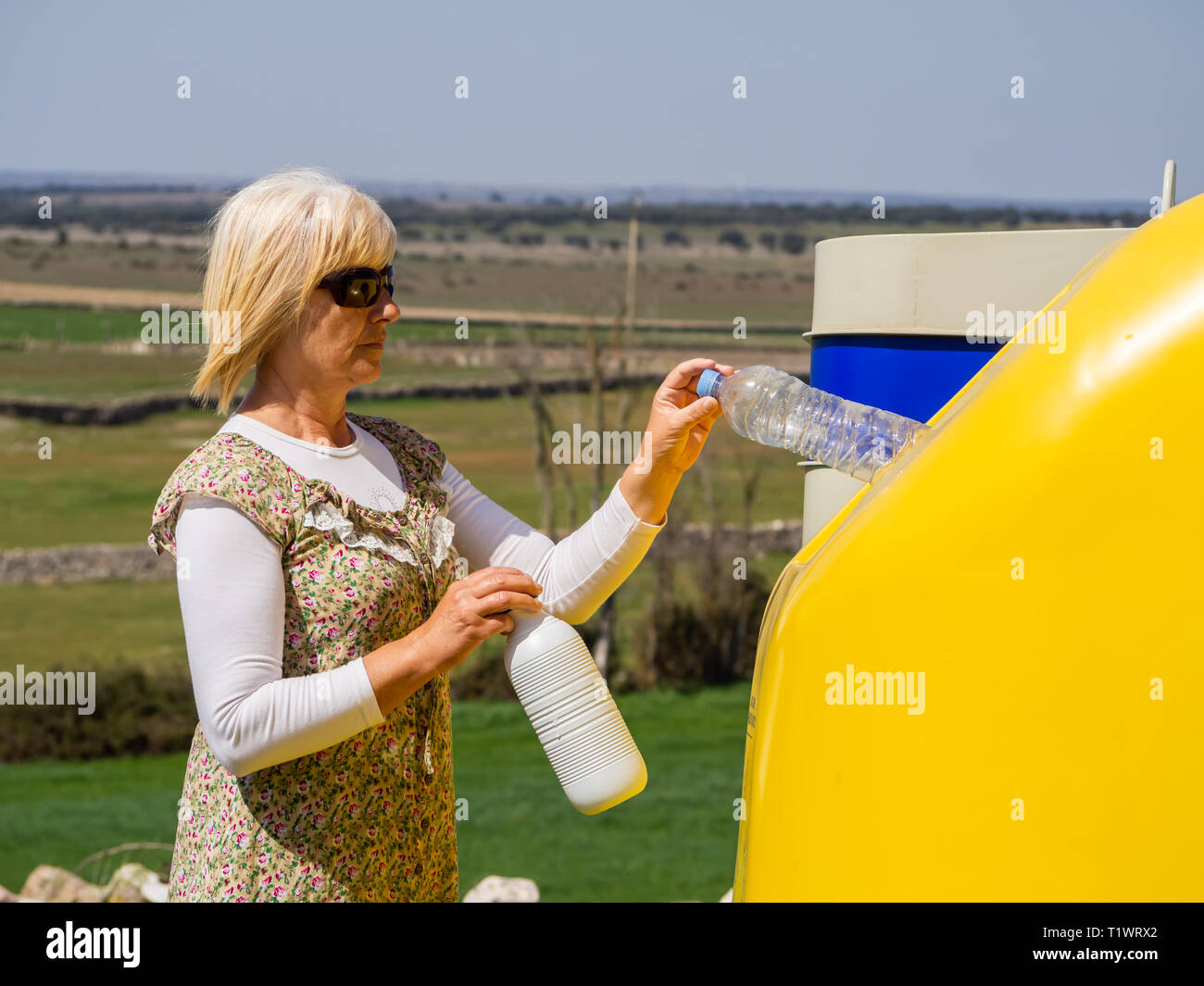 A mature woman pulling a plastic bottle in a yellow bin for recycling plastic - Stock Image