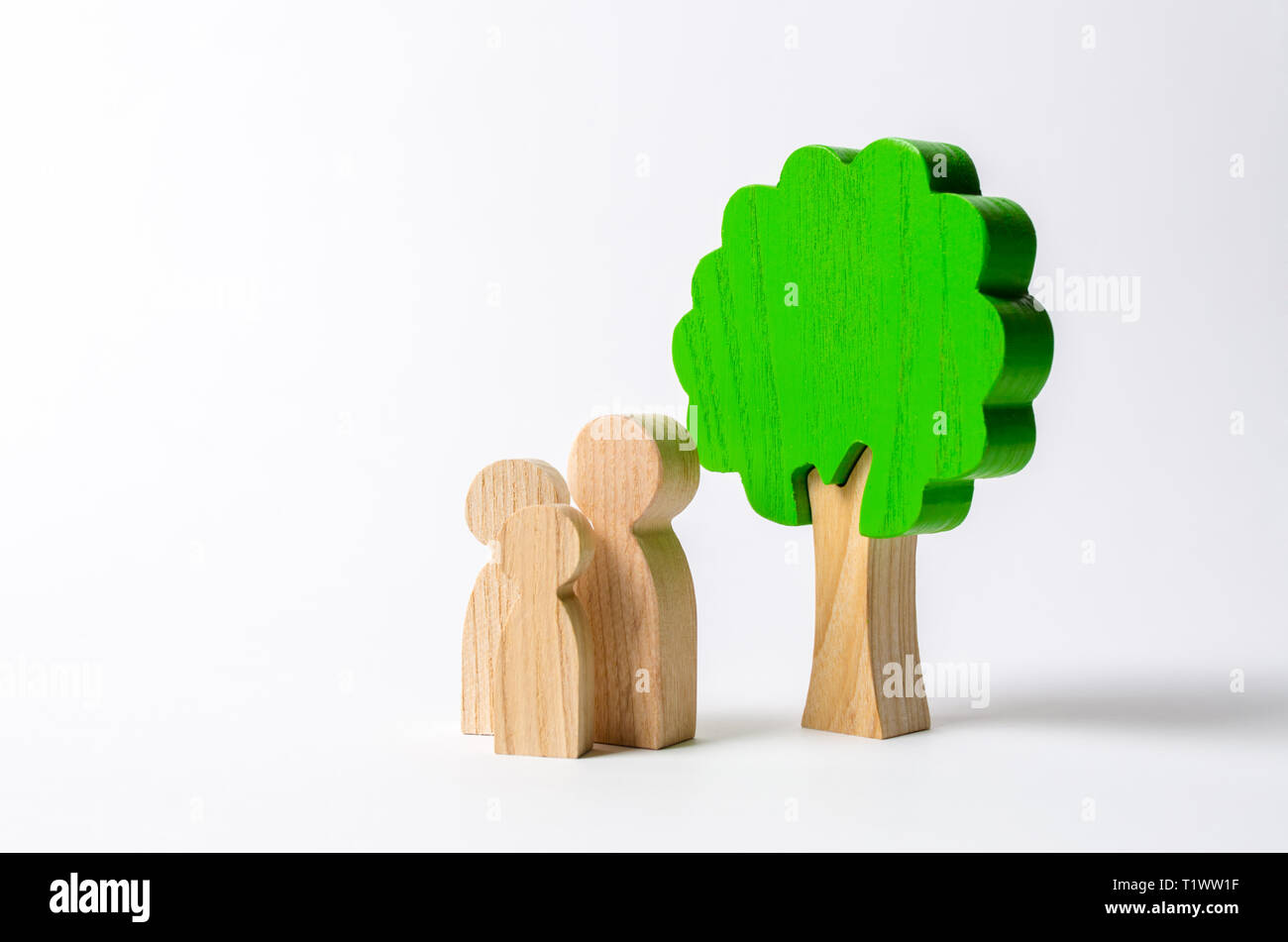 Family figures are standing near the tree. Pastime with family, kinship and parenting. Instilling good qualities and values in a healthy society. The  - Stock Image