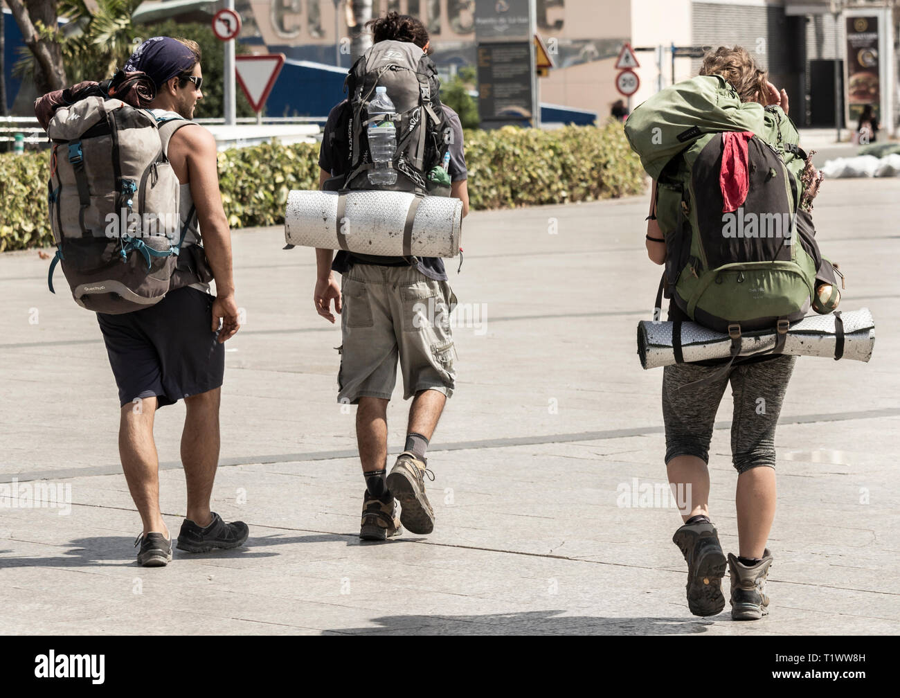 Three young people carrying large rucksacks. Gap year, adventure, travel... - Stock Image