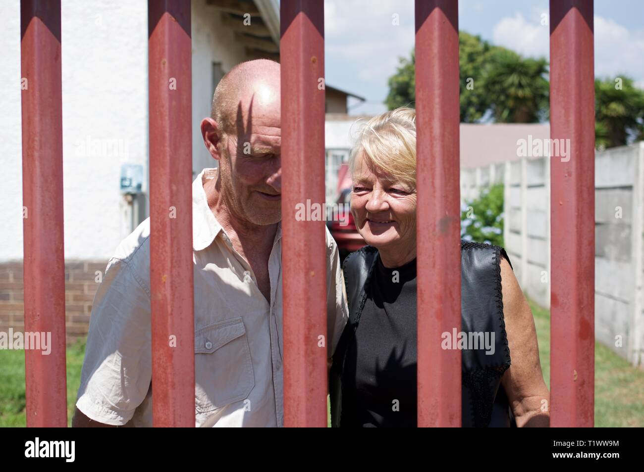 Afrikaner couple standing behind their barred security gate in Johannesburg - Stock Image