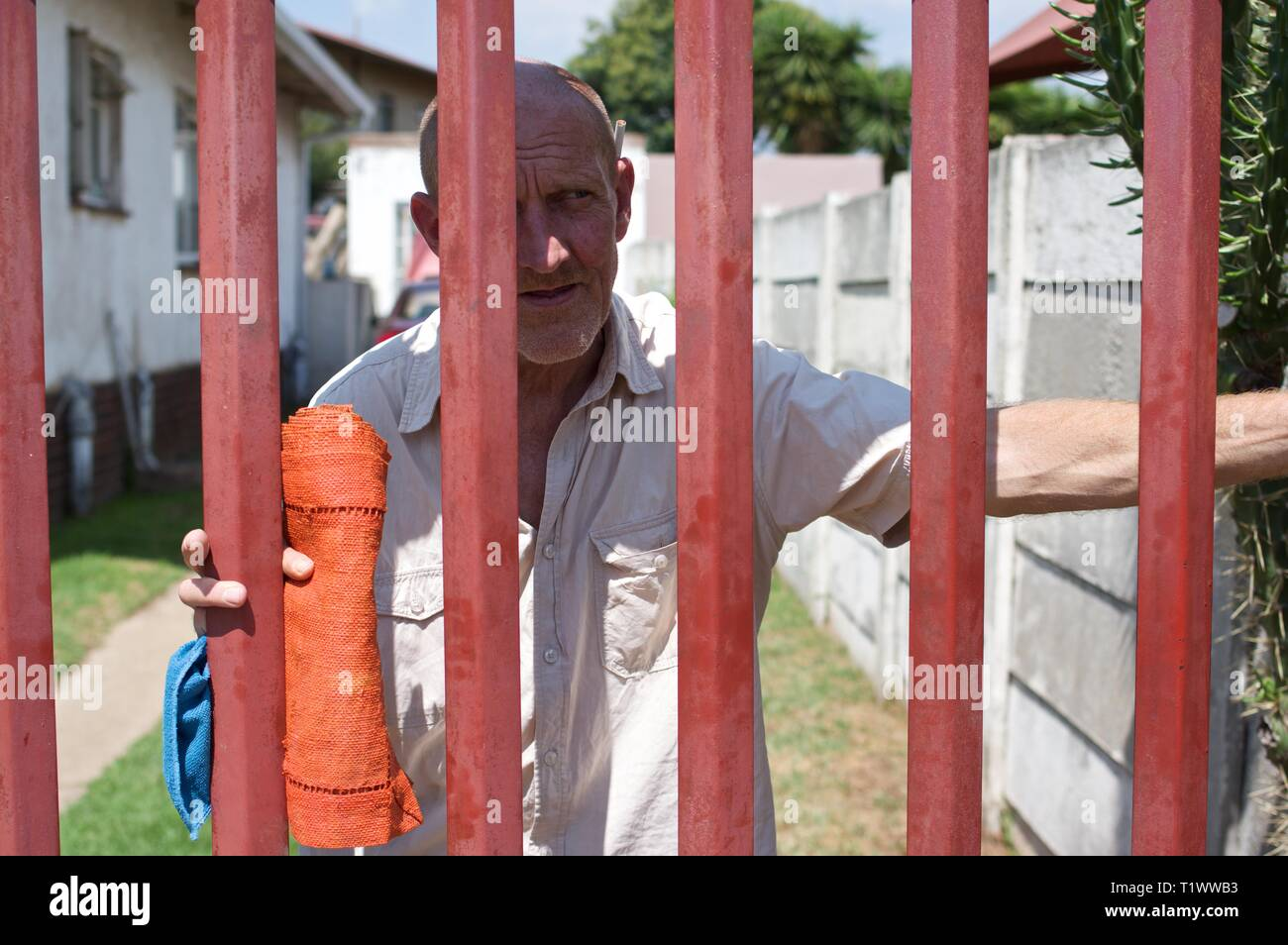 Middle aged Afrikaner man looks out from behind his security gate in Johannesburg - Stock Image