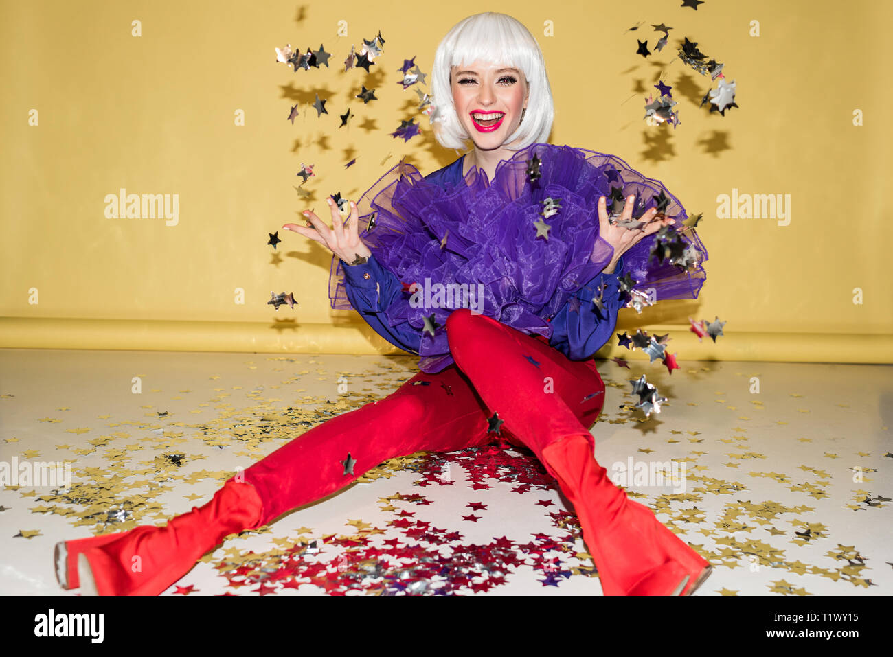 Laughing woman in red pants throwing out sparkle confetti on yellow background - Stock Image