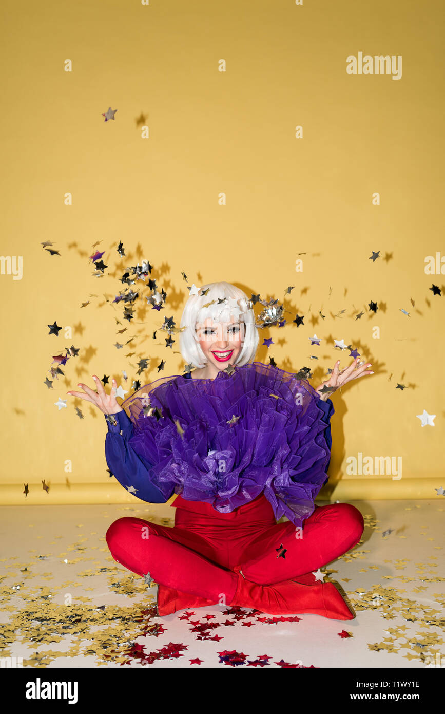 Happy girl in white wig sitting on floor with crossed legs and throwing out star confetti on yellow background - Stock Image