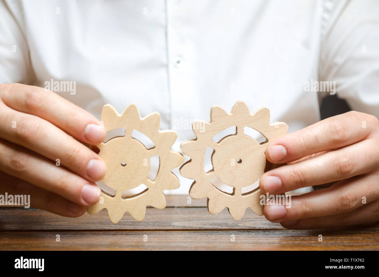 Businessman in white shirt connects two wooden gears. Symbolism of establishing business processes and communication. Improving work efficiency, estab - Stock Image