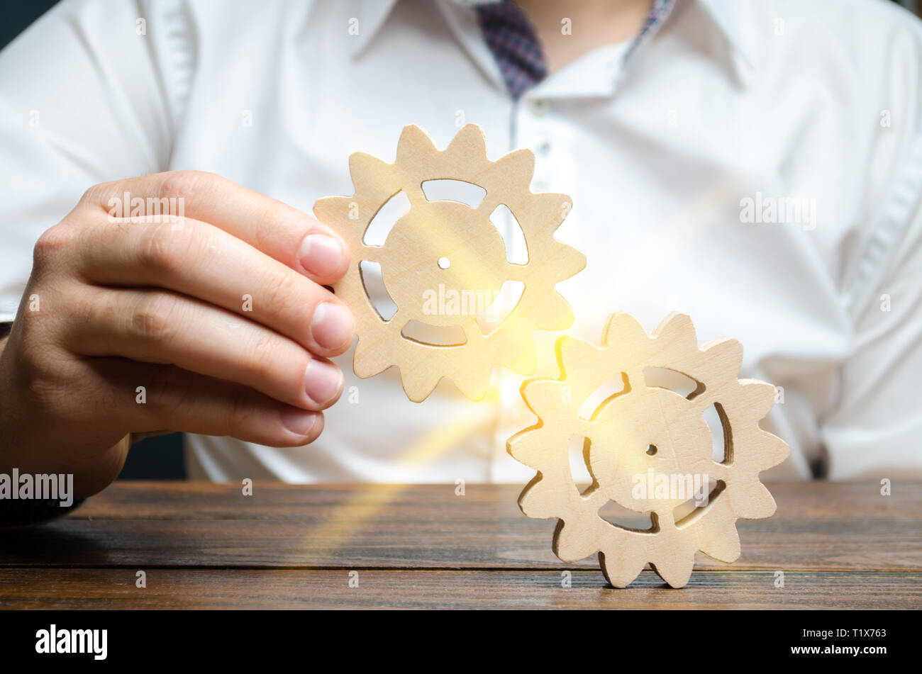 Businessman in white shirt connects two wooden gears. Symbolism of establishing business processes and communication. Increase efficiency and producti - Stock Image