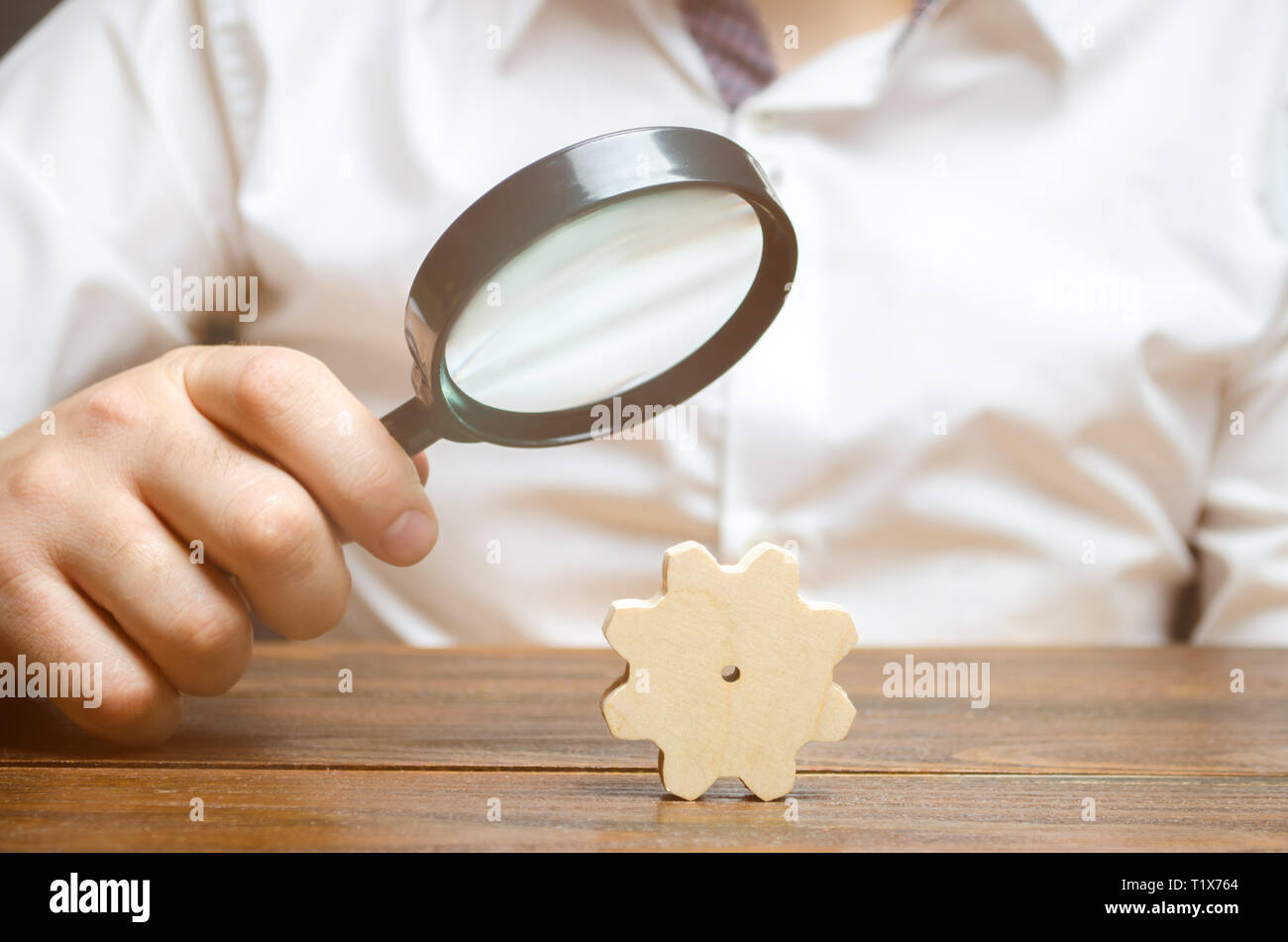 Businessman examines a wooden gear through a magnifying glass. study and analysis of business processes and subjects. A cog from a big business machin - Stock Image