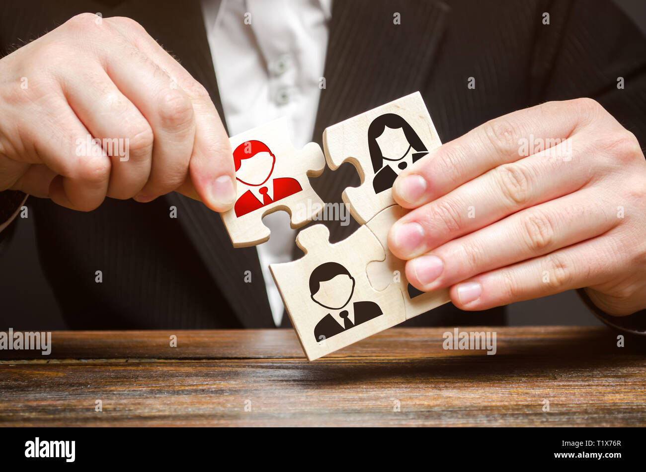 A businessman collects puzzles symbolizing a team of employees. The concept of the organization of the team and the business hierarchy. Management. Th Stock Photo