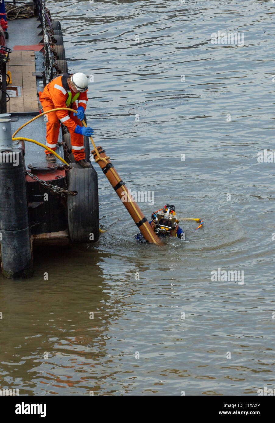 Diver lift a pressure cleaning pipe with the help of a maintenance crew member onto a boat after unblocking an underwater drain in the River Thames. - Stock Image