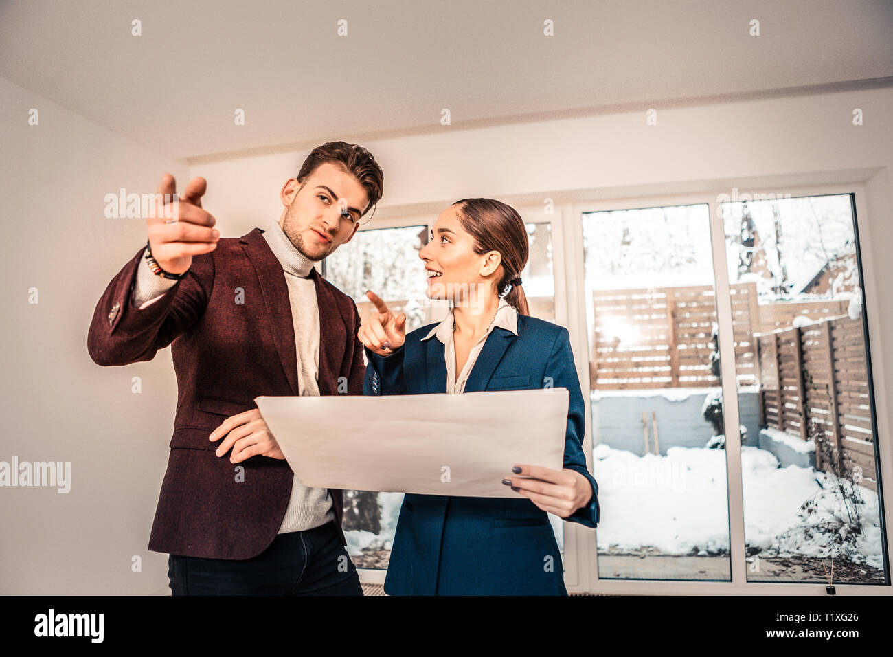 Handsome businessman asking questions to professional realtor - Stock Image