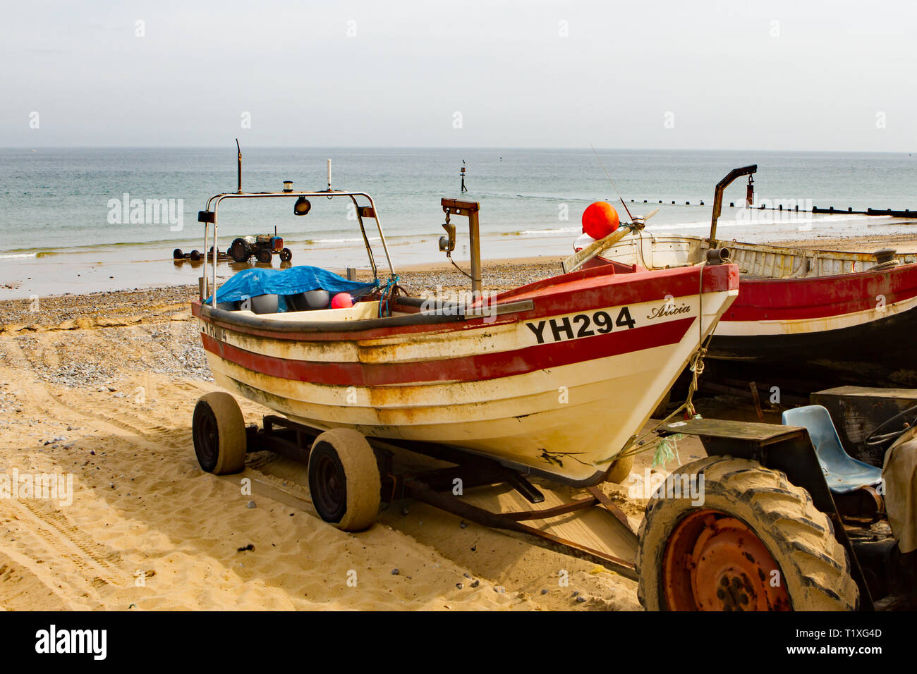 An old traditional wooden fishing boat on Cromer beach in need of some TLC - Stock Image