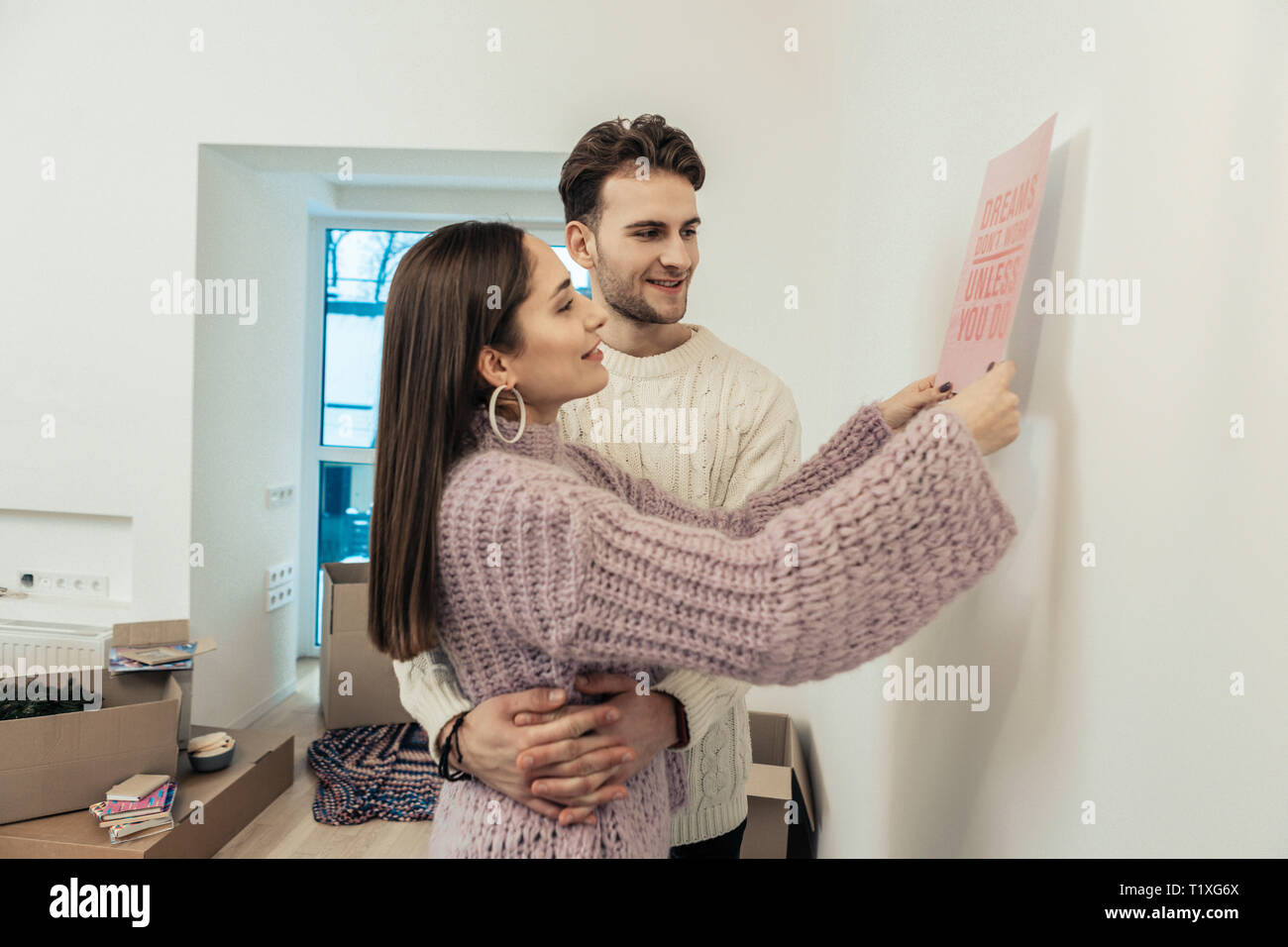 Wife outing some poster on the wall while husband hugging her - Stock Image