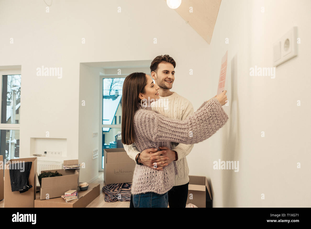 Handsome dark-haired man hugging his wife decorating the wall - Stock Image