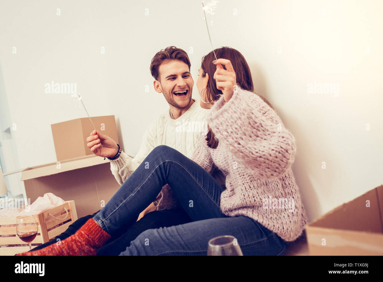 Handsome man laughing while firing sparklers with his wife - Stock Image