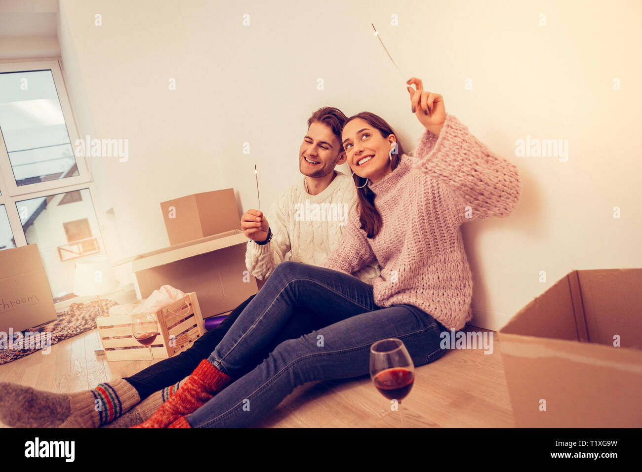Couple celebrating their moving drinking wine and firing sparklers - Stock Image