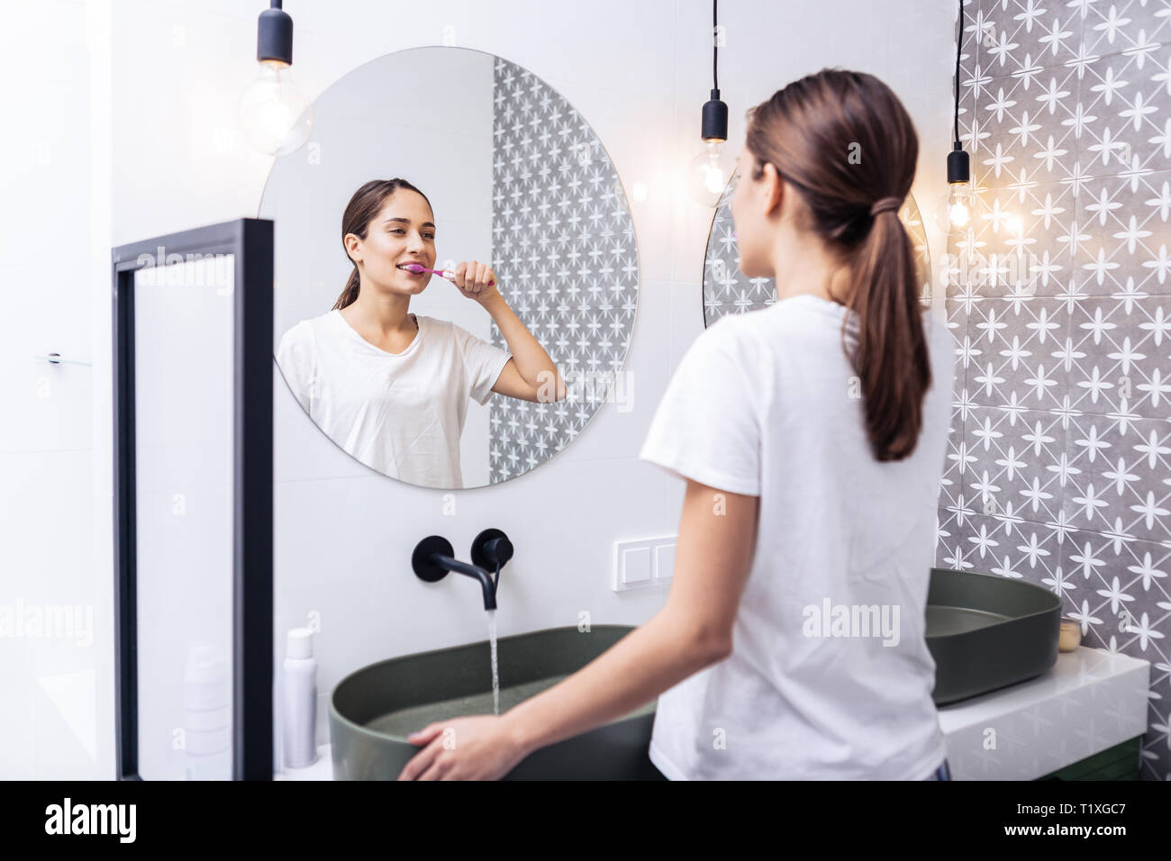 Appealing woman brushing teeth standing in the bathroom - Stock Image