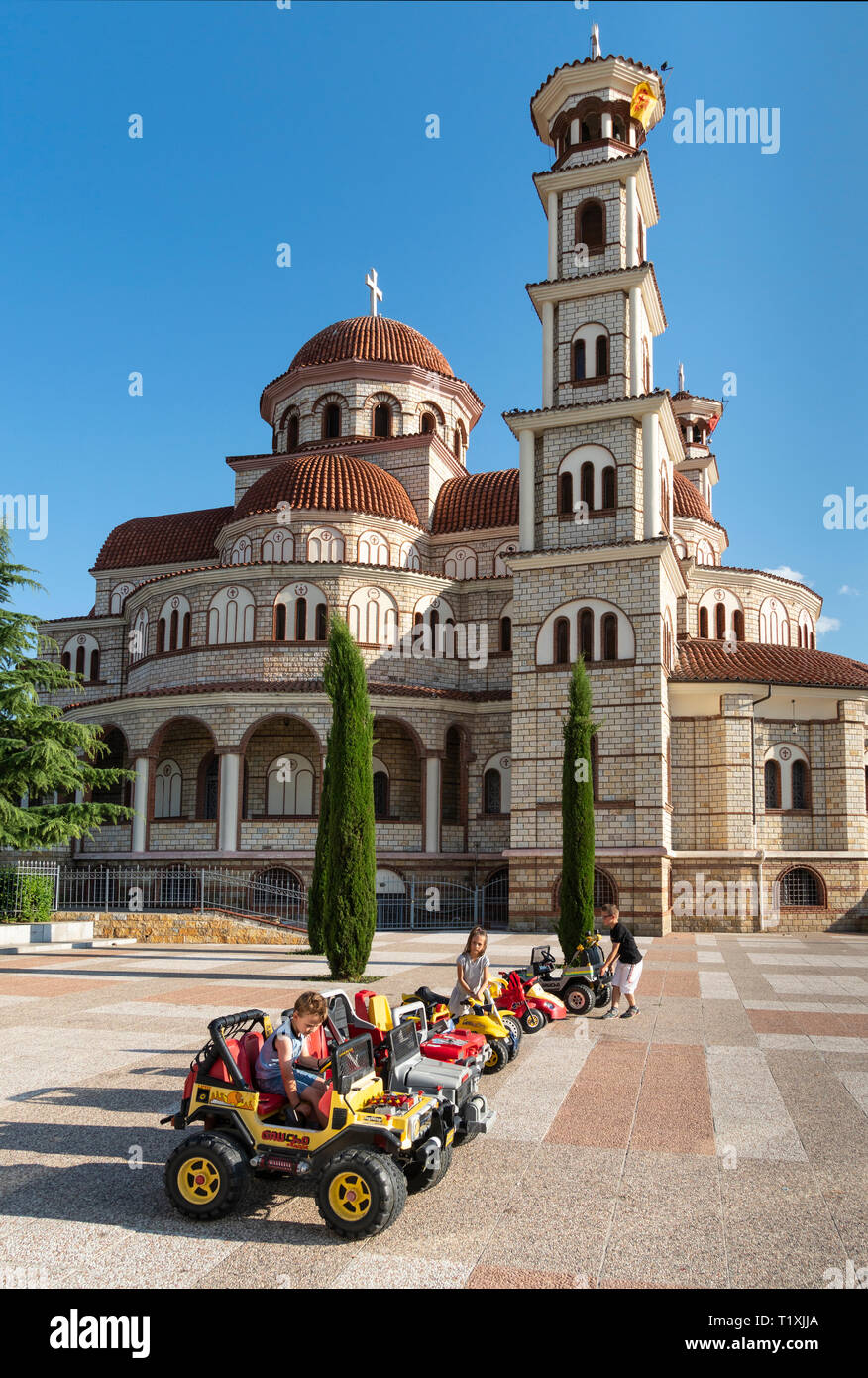 Children playing on miniature cars in front of Korca's Orthodox Cathedral, Korca, South eastern Albania. - Stock Image