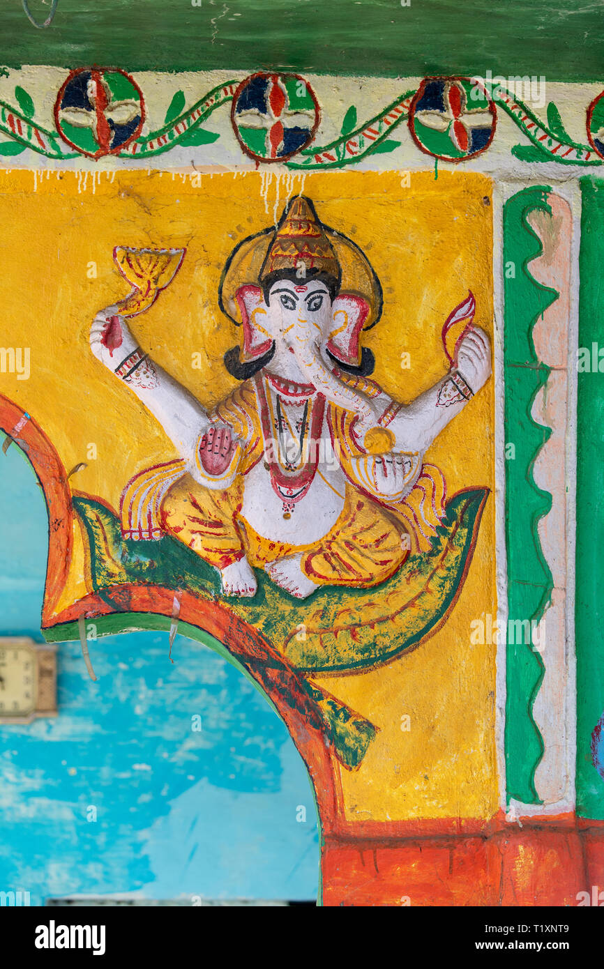 A variety of Hindu deities are carved and colorfully painted on the outside of a Hindu temple of worship in rural India Stock Photo