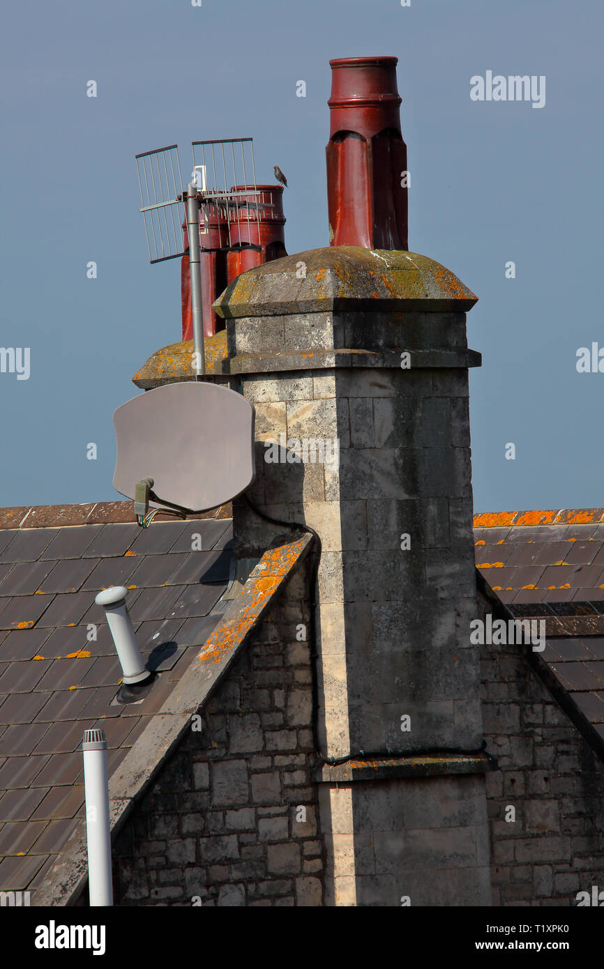 Sat on the top of the roof these fluted Chimney pots have withstood heat and cold and all the weather the area has thrown at them for many years. - Stock Image