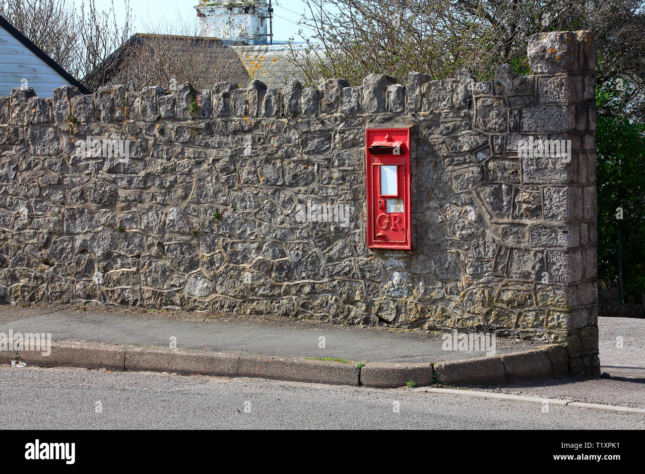 An old King George era letter box embedded in a wall adjacent to the main road through the village, now replaced by a nearby free standing box. - Stock Image