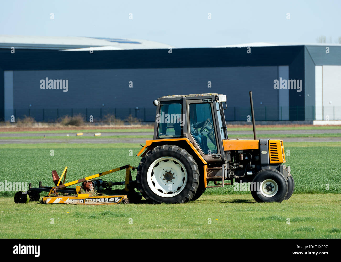 A tractor mowing grass at Wellesbourne Airfield, Warwickshire, UK - Stock Image