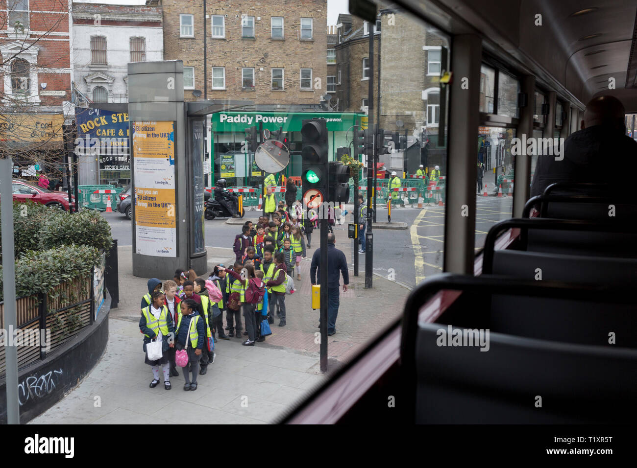 A group of Primary school age cross the road in Camberwell, Southwark, on 27th March 2019, in London, England - Stock Image