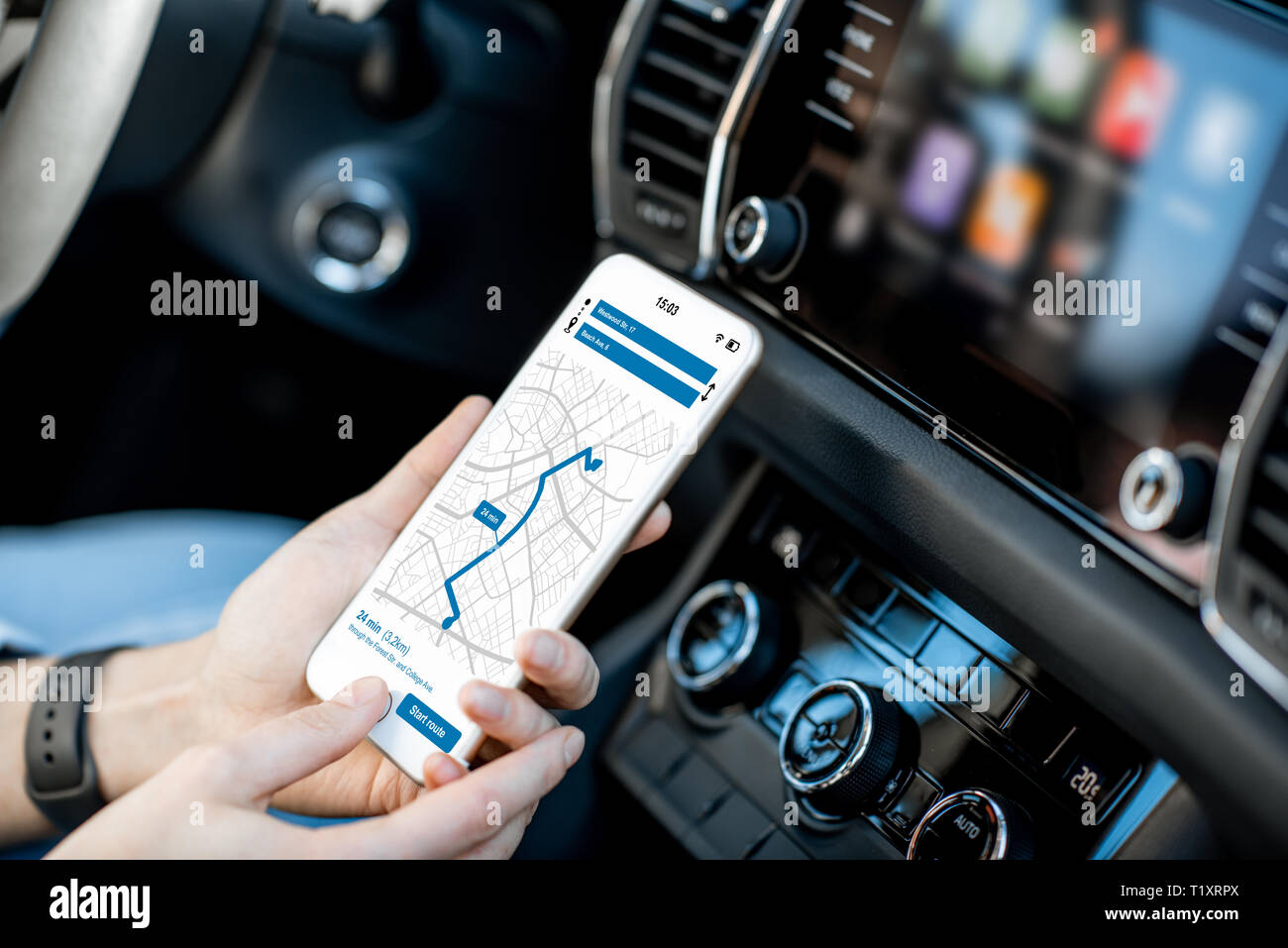 Close-up of a smartphone with navigation app in the modern car with monitor on the background - Stock Image