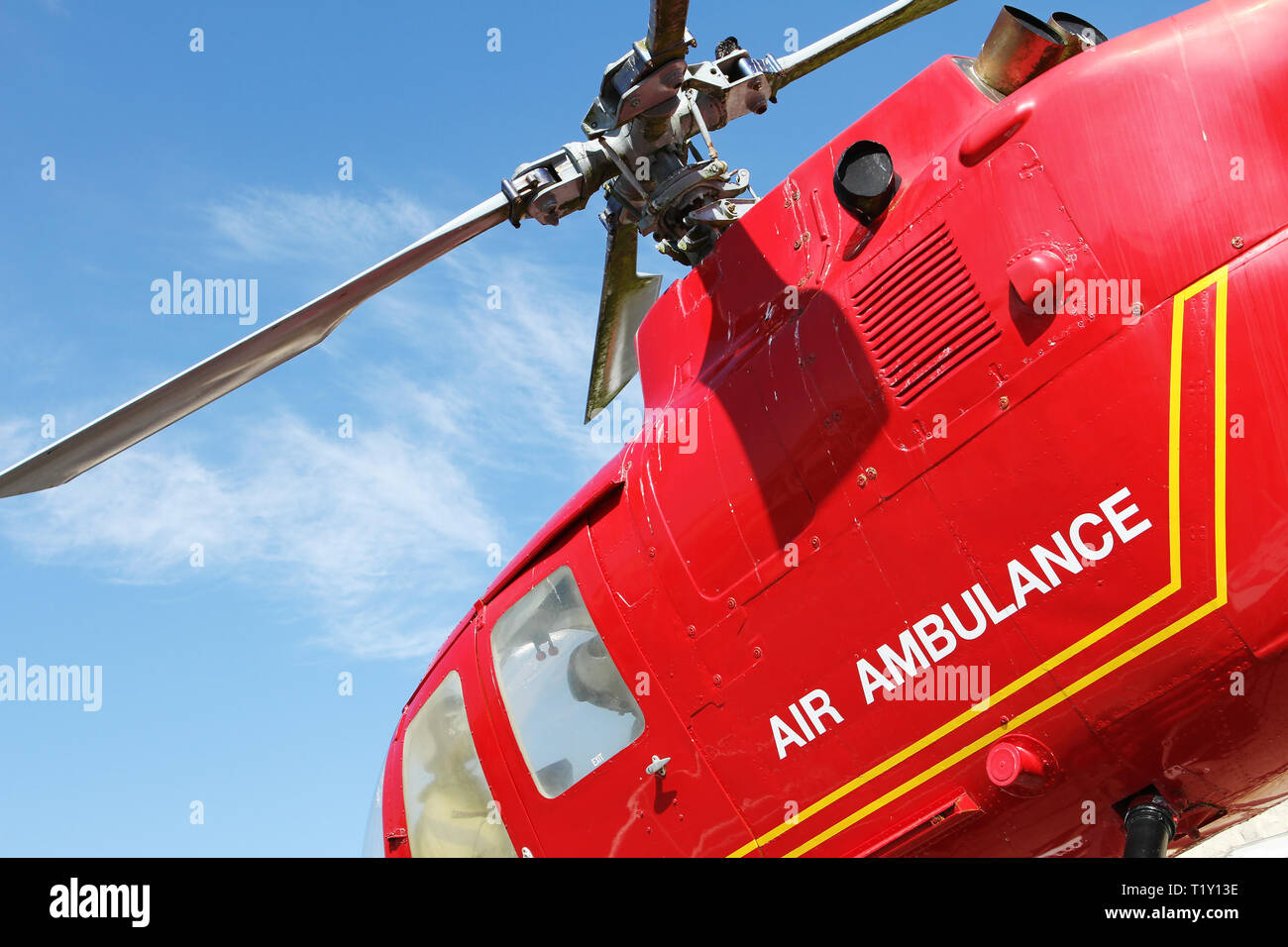 Red helicopter of air ambulance isolated on blue sky background. Detail of the helicopter blades. Cornwall, UK - Stock Image