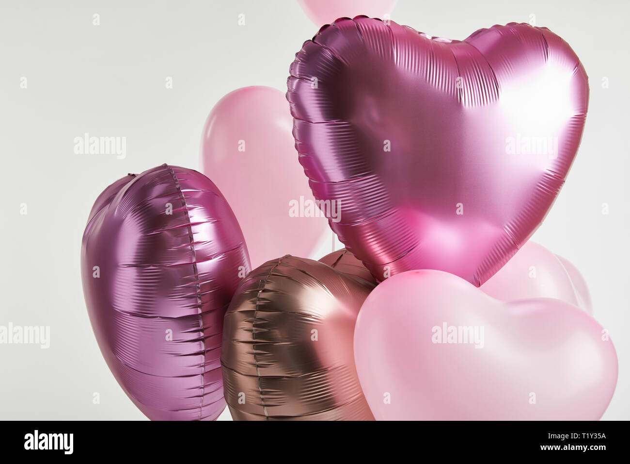 heart-shaped pink and golden balloons isolated on white Stock Photo
