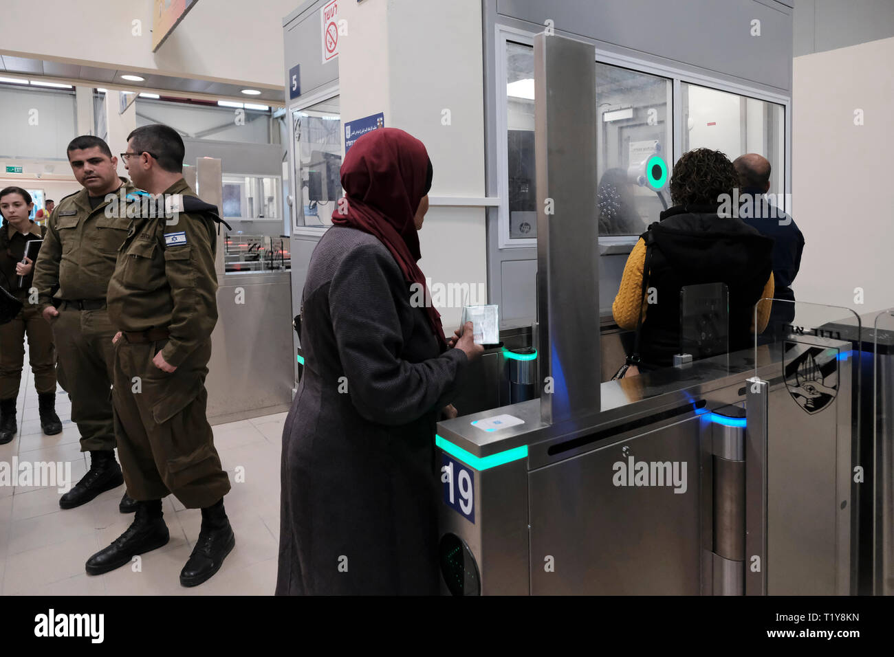 Qalandya, ISRAEL 28th March - A Palestinian woman on her way to Jerusalem crossing turnstile gate with bio-metric system at the newly renovated Kalandia or Qalandiya Checkpoint between Jerusalem and Ramallah on 28 March 2019. The Qalandiya Checkpoint's $11 million renovation was carried out in order to enhance the commute of thousands of Palestinians every day, mostly with the help of new identification stations with improved technology. Credit: Eddie Gerald/Alamy Live News - Stock Image