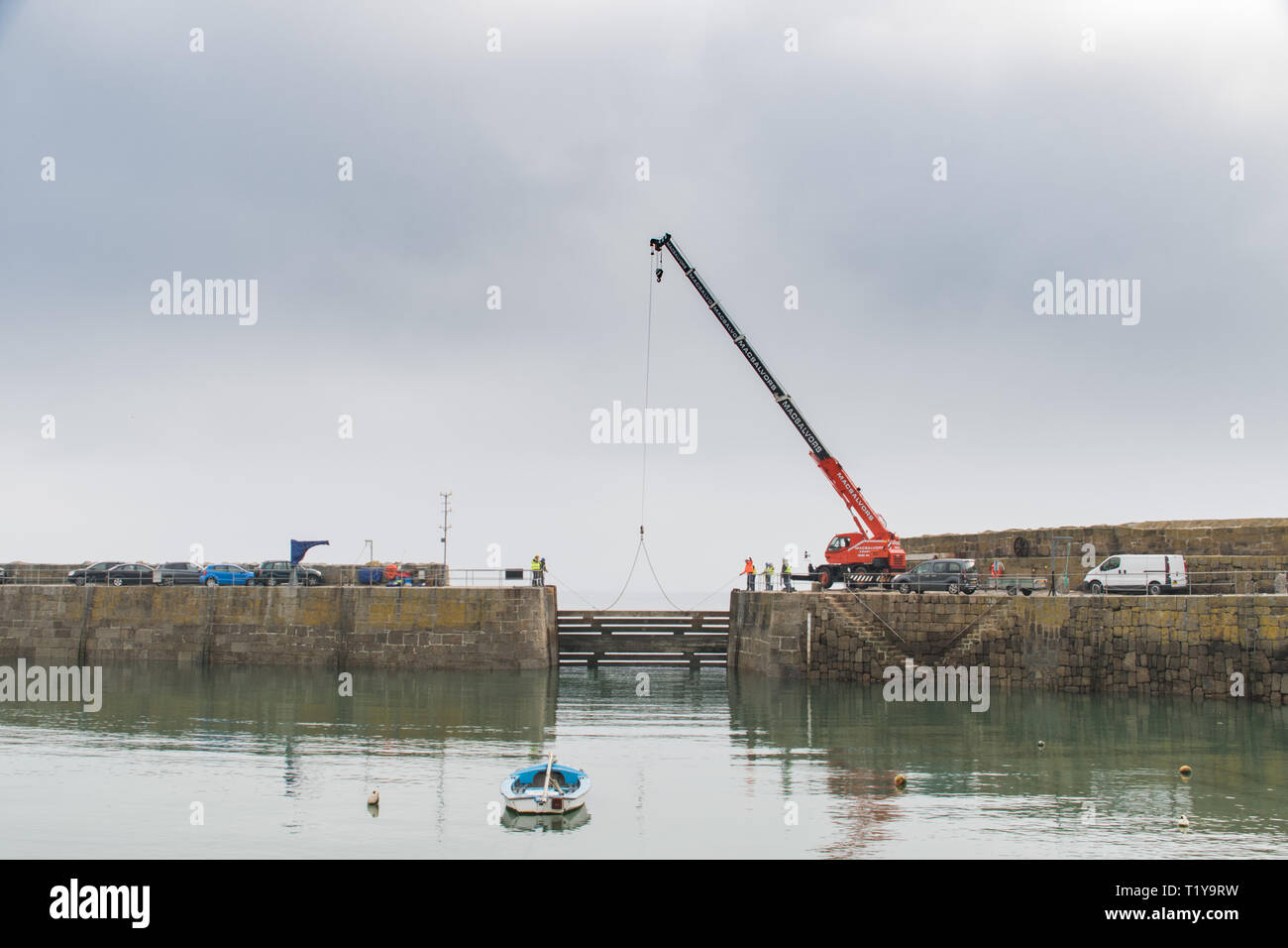 """Mousehole, Cornwall, UK. 29th Mar, 2019. As the clocks go forward this weekend, heradling the start of British Summer Time, so the giant timber """"baulks"""" that protect Mousehole harbour during the winter months are lifted out, allowing the tiny fishing fleet, as well as leisure boats in and out of the harbour. Credit: Simon Maycock/Alamy Live News Stock Photo"""