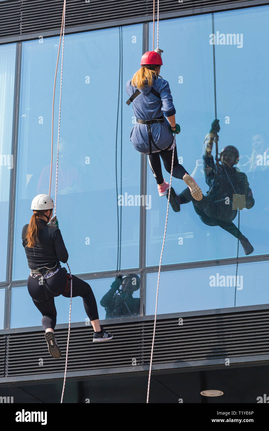 Bournemouth, Dorset, UK. 29th Mar, 2019. Staff working for telecommunications provider 4Com abseil down their new office building at One Lansdowne Plaza in Bournemouth which is 100ft high. They are raising funds for Hope Housing and Hope AOK Rucksack Appeal who provide support to homeless in Bournemouth. A lovely warm sunny day for the descent! Two women abseil down while friends and colleagues look out. Credit: Carolyn Jenkins/Alamy Live News - Stock Image
