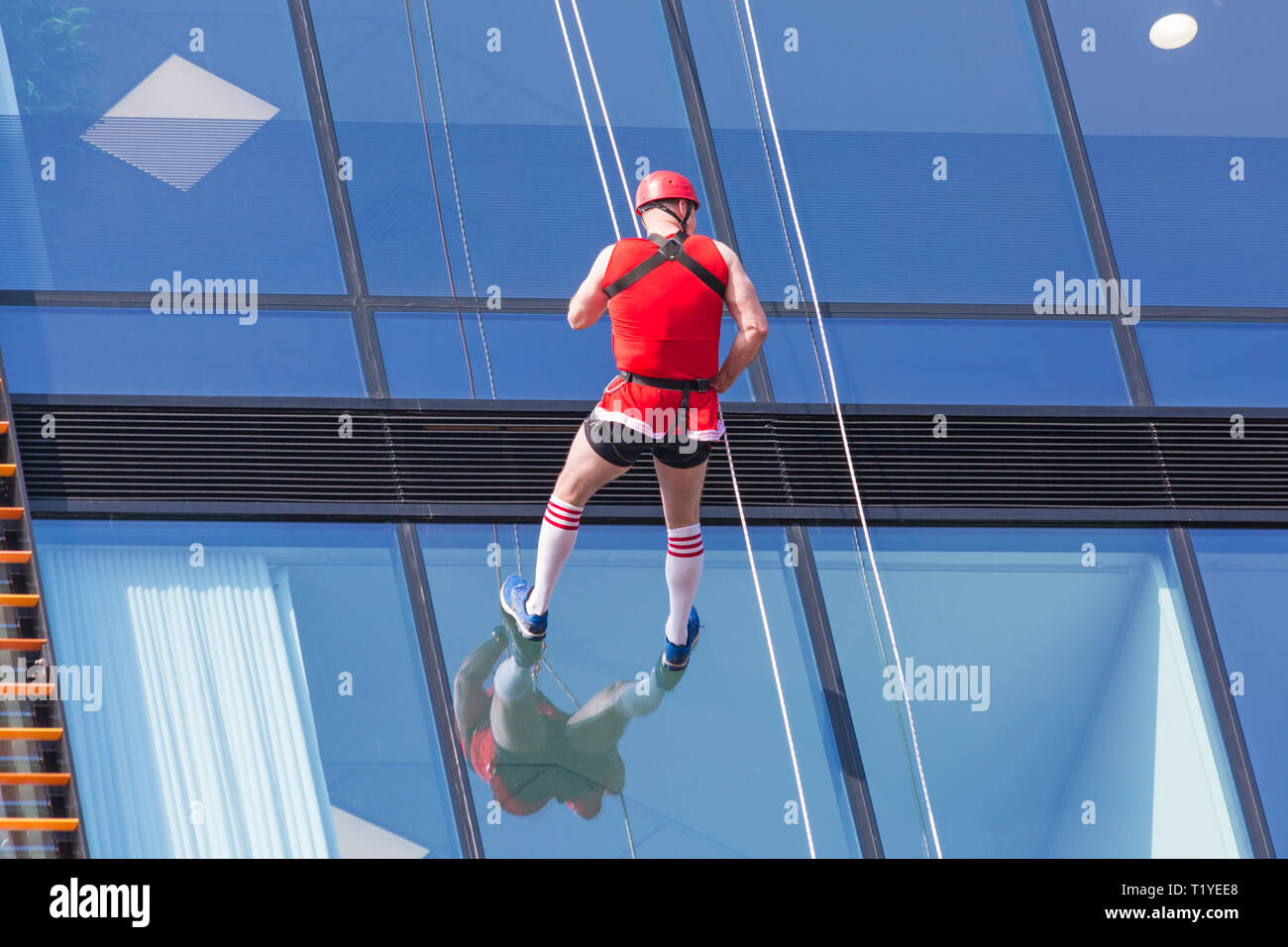 Bournemouth, Dorset, UK. 29th Mar, 2019. Staff working for telecommunications provider 4Com abseil down their new office building at One Lansdowne Plaza in Bournemouth which is 100ft high. They are raising funds for Hope Housing and Hope AOK Rucksack Appeal who provide support to homeless in Bournemouth. A lovely warm sunny day for the descent! Man abseils down. Credit: Carolyn Jenkins/Alamy Live News - Stock Image