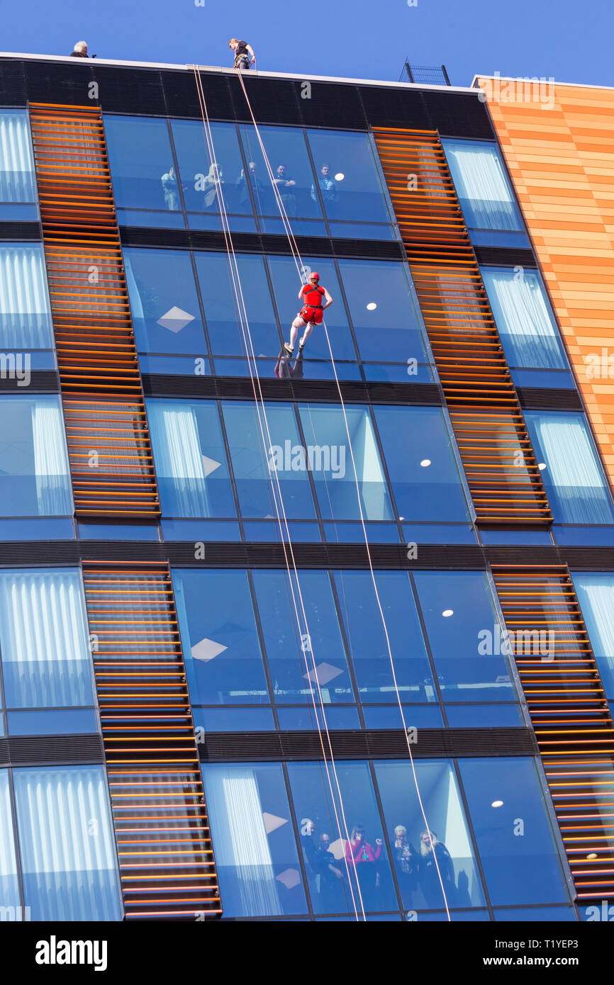 Bournemouth, Dorset, UK. 29th Mar, 2019. Staff working for telecommunications provider 4Com abseil down their new office building at One Lansdowne Plaza in Bournemouth which is 100ft high. They are raising funds for Hope Housing and Hope AOK Rucksack Appeal who provide support to homeless in Bournemouth. A lovely warm sunny day for the descent! Woman abseils down while friends and colleagues look out.  Credit: Carolyn Jenkins/Alamy Live News - Stock Image