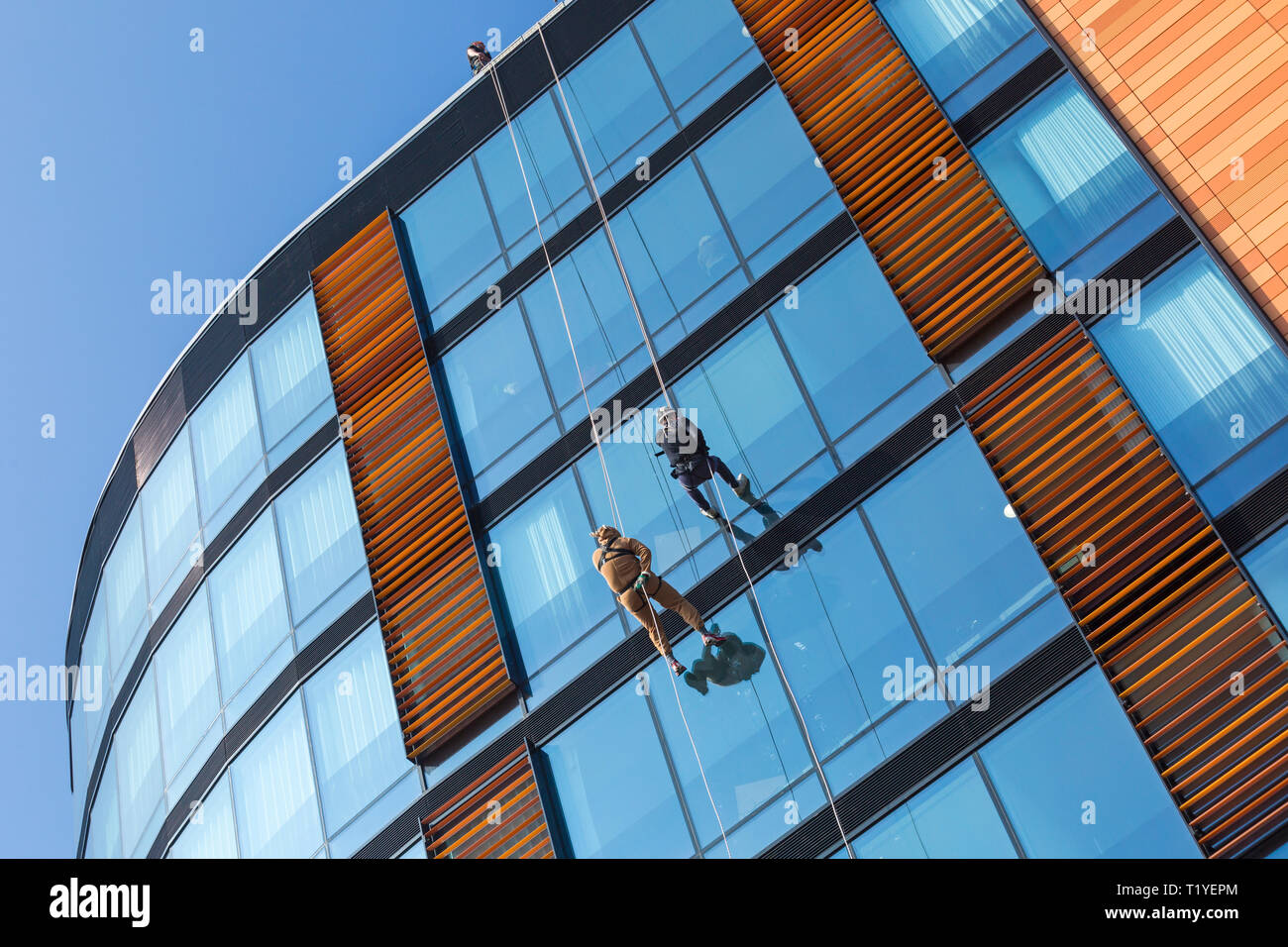 Bournemouth, Dorset, UK. 29th Mar, 2019. Staff working for telecommunications provider 4Com abseil down their new office building at One Lansdowne Plaza in Bournemouth which is 100ft high. They are raising funds for Hope Housing and Hope AOK Rucksack Appeal who provide support to homeless in Bournemouth. A lovely warm sunny day for the descent! Men abseil down. Credit: Carolyn Jenkins/Alamy Live News - Stock Image