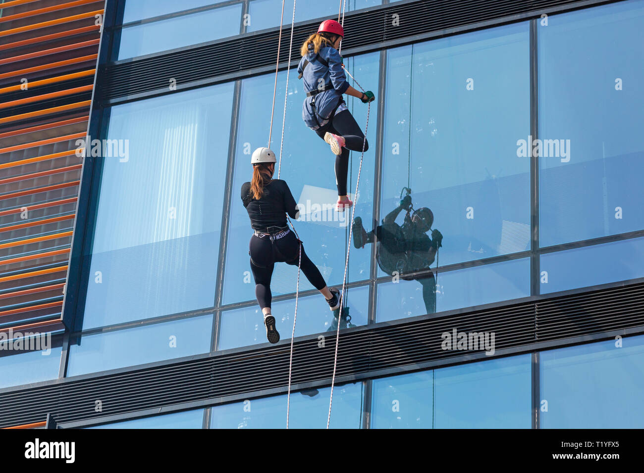 Bournemouth, Dorset, UK. 29th Mar, 2019. Staff working for telecommunications provider 4Com abseil down their new office building at One Lansdowne Plaza in Bournemouth which is 100ft high. They are raising funds for Hope Housing and Hope AOK Rucksack Appeal who provide support to homeless in Bournemouth. A lovely warm sunny day for the descent! Two women abseil down. Credit: Carolyn Jenkins/Alamy Live News - Stock Image