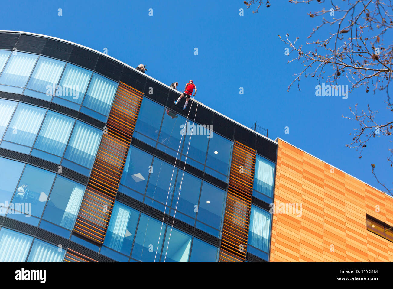 Bournemouth, Dorset, UK. 29th Mar, 2019. Staff working for telecommunications provider 4Com abseil down their new office building at One Lansdowne Plaza in Bournemouth which is 100ft high. They are raising funds for Hope Housing and Hope AOK Rucksack Appeal who provide support to homeless in Bournemouth. A lovely warm sunny day for the descent!  Man abseils down while friends and colleagues look out. Credit: Carolyn Jenkins/Alamy Live News - Stock Image