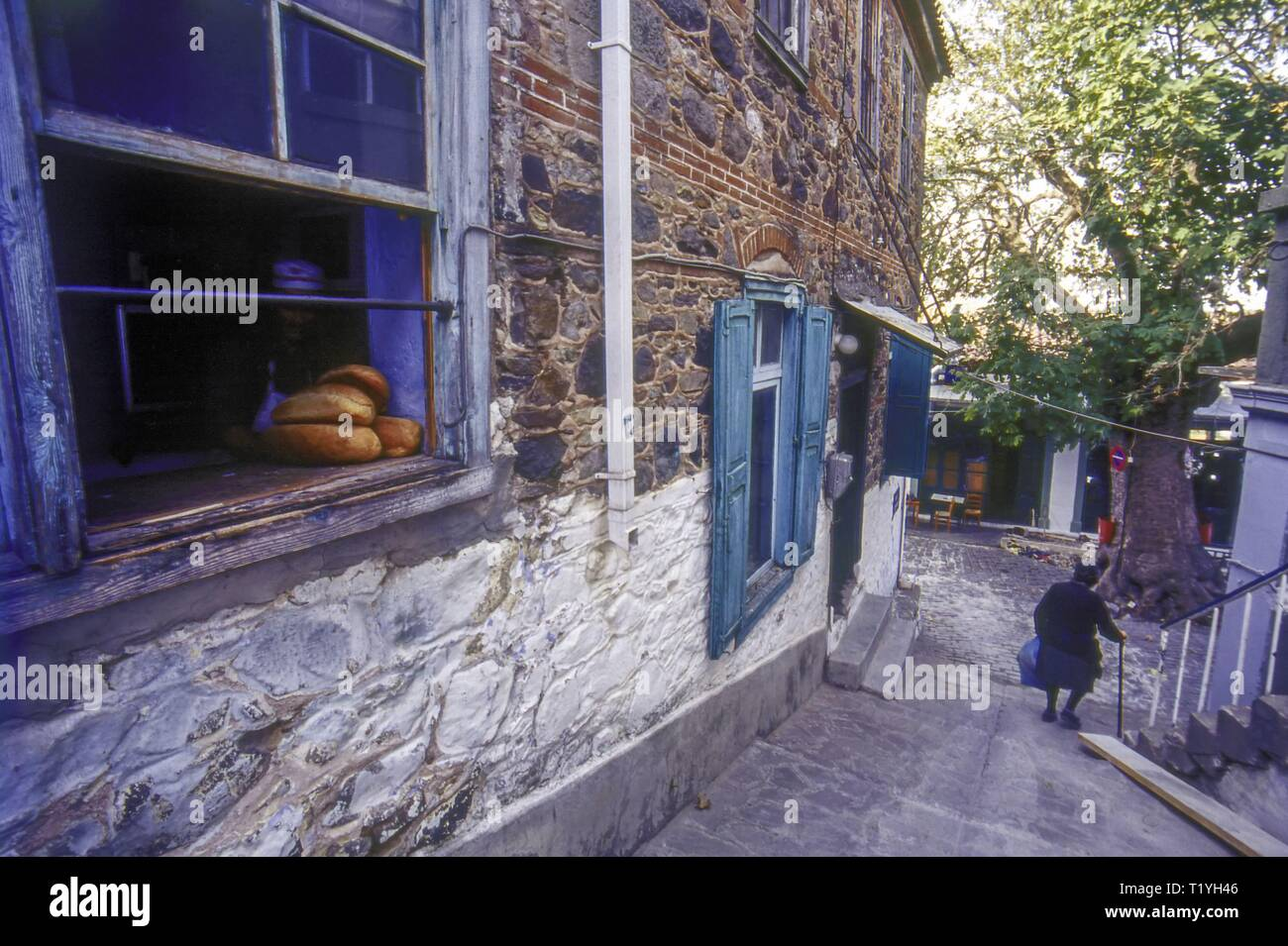 An Old Greek Woman leaving the Bakery in Vatoussa Village, Lesvos, Greece - Stock Image