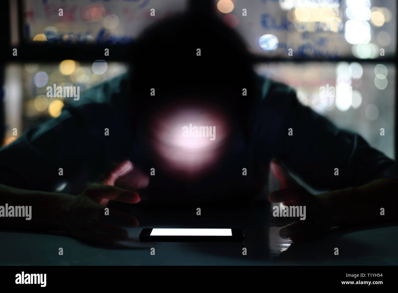 smartphone addiction depression. blur motion face of Man looking at mobile phone in a room. night light of city skyline bokeh outside of the window. m - Stock Image