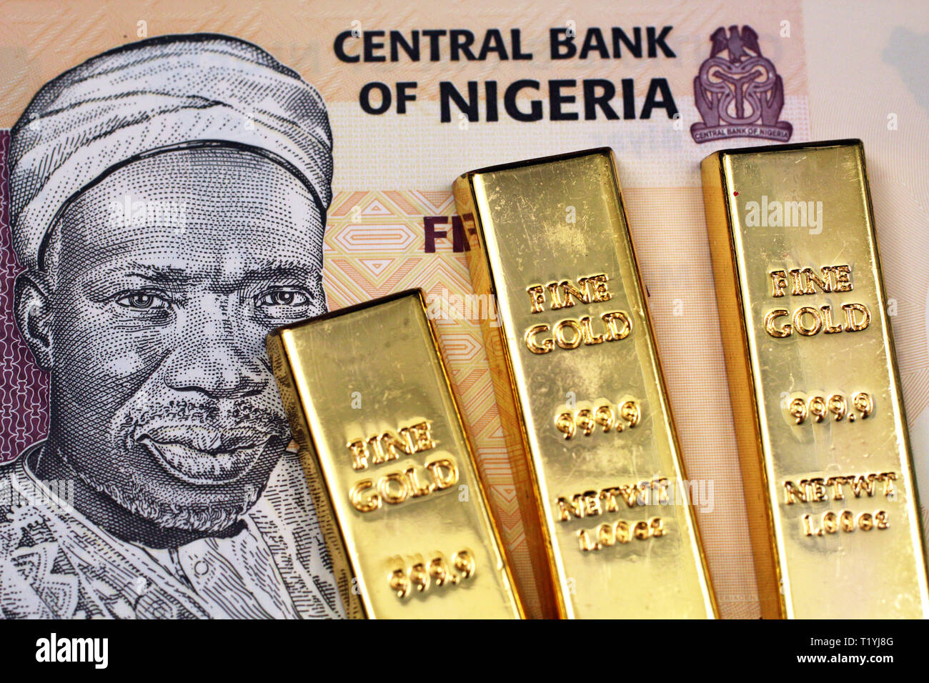 A five Nigerain naira bank note with three small gold bars close up in macro - Stock Image