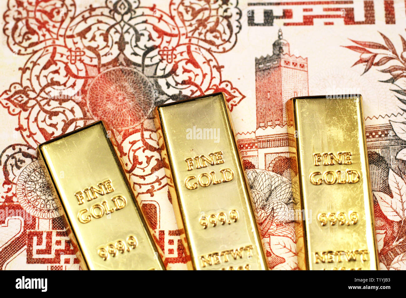 A close up image of a two hundred Algerian dinar bank note with three gold bars in macro - Stock Image