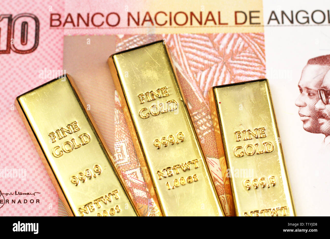 A macro image of three small golden ingots with a ten Angolan Kwanza bank note close up - Stock Image