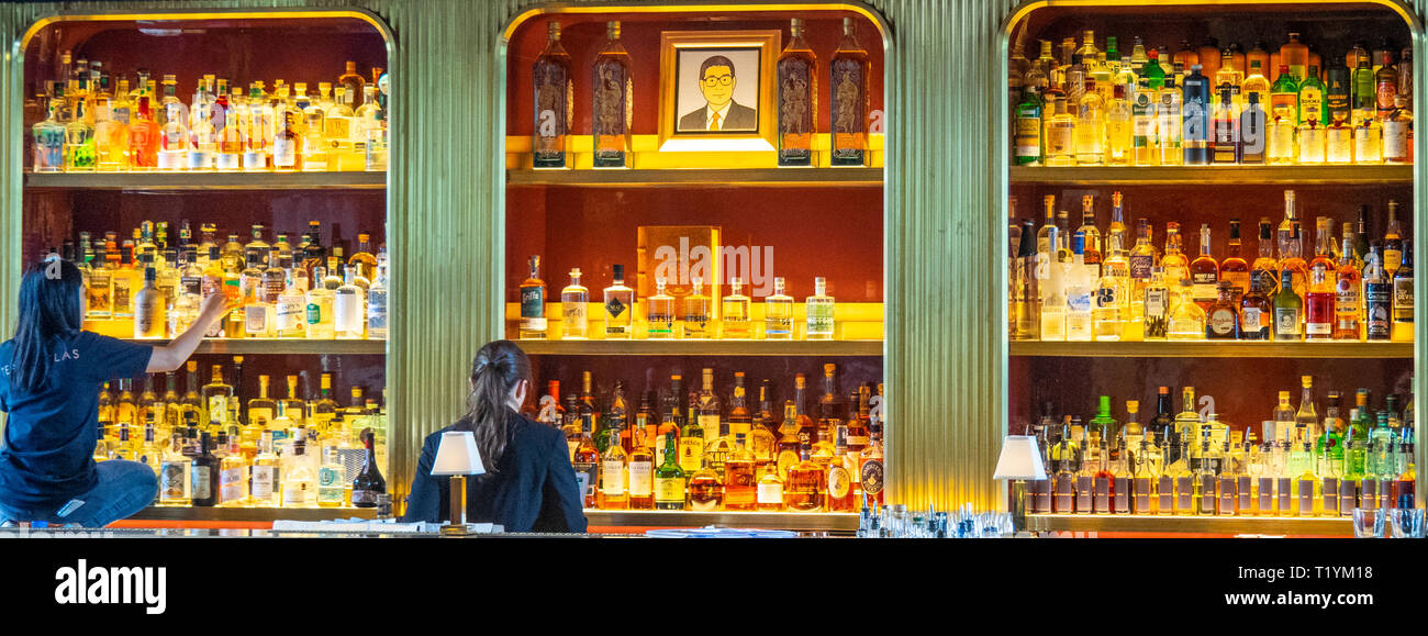 Two women cleaning gin bottles in glass cabinet of Atlas Bar in the Lobby of Parkview Square Singapore. - Stock Image