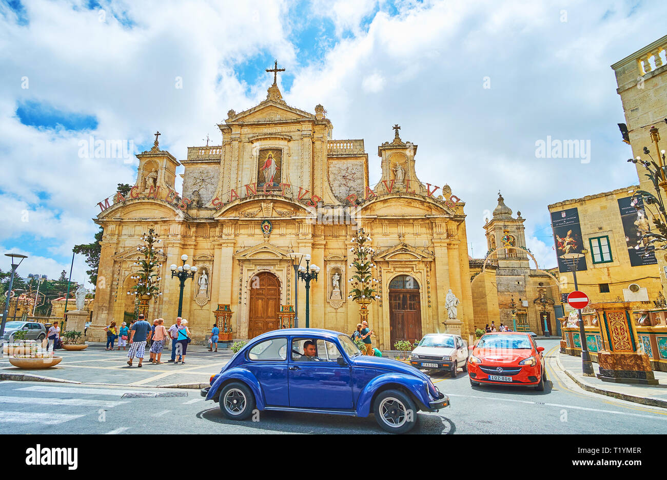 RABAT, MALTA - JUNE 16, 2018: The vintage Volkswagen Kafer (Beetle) car drives along the San Pawl Square with a view on Church of St Paul on the backg - Stock Image