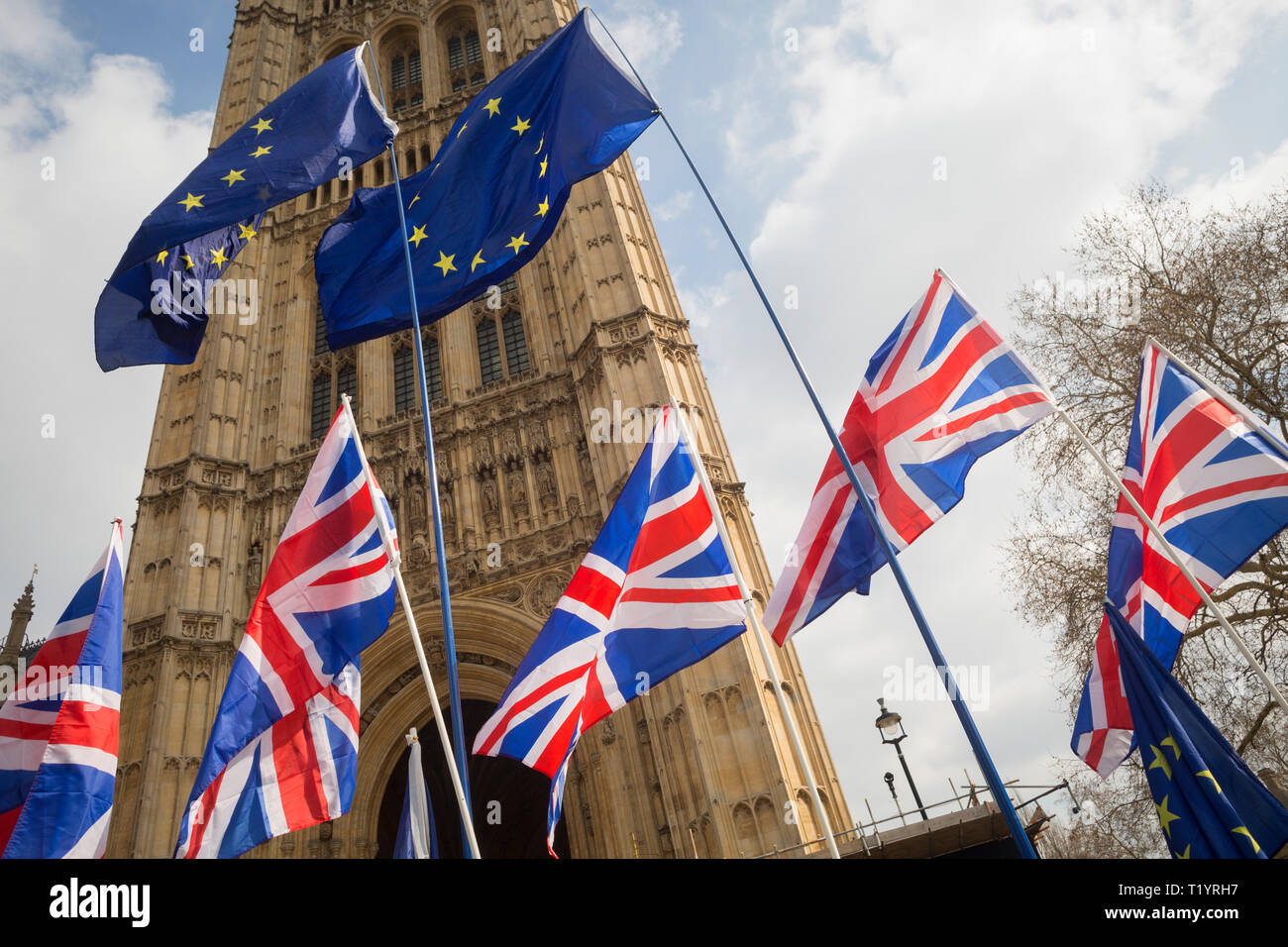 As MPs decide on how to progress with Brexit parliamentary procedure, EU and Union Jack flags fly outside the UK Parliament in Westminster, on 28th March 2019, in London, England - Stock Image