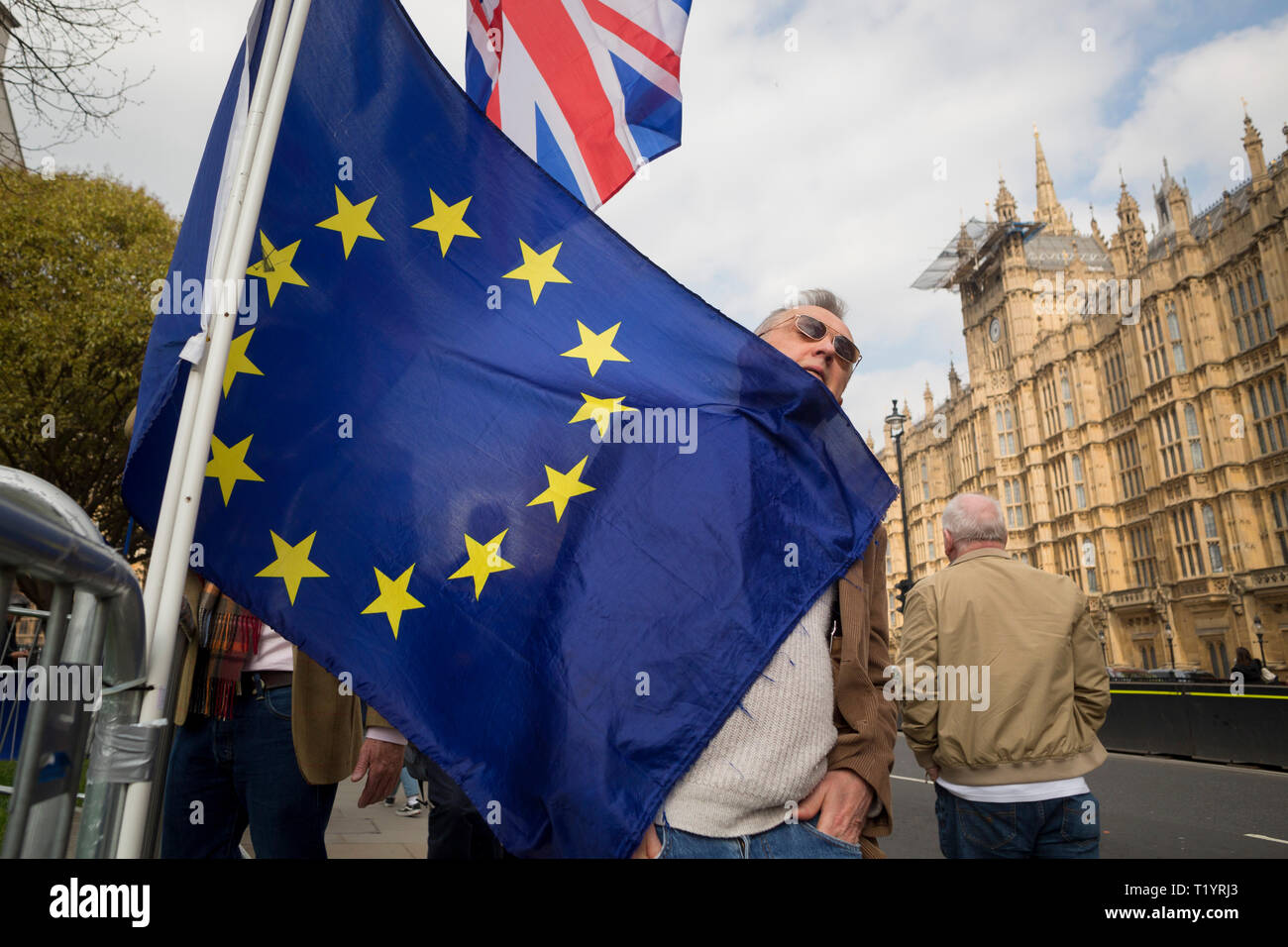 As MPs decide on how to progress with Brexit parliamentary procedure, and EU flag catches the face of a passer-by outside the UK Parliament in Westminster, on 28th March 2019, in London, England - Stock Image