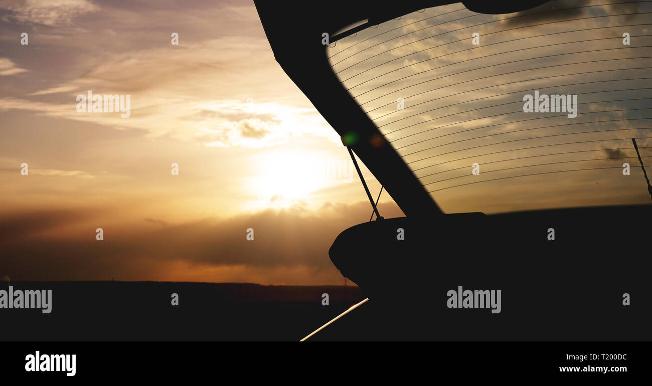 Outdoor car trunk at sunset, photo against the sun - travel concept - Stock Image